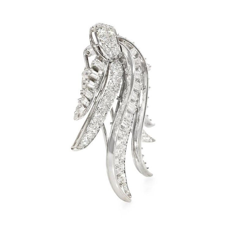 A Retro diamond clip brooch of draped tendril design, in platinum.  Atw round and baguette cut diamonds 10.00 cts.  Excellent quality and workmanship