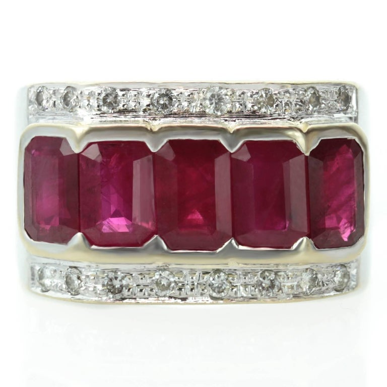 This stylish retro band is made in 18k white gold and features 5 emerald-cut 4.0mm x 6.0mm rubies set yellow gold and surrounded by sparkling round diamonds. Measurements: 0.47