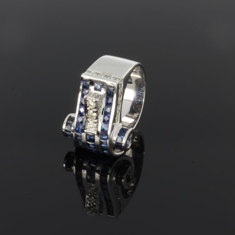 Set with 3 brilliant-cut diamonds with a total weight of 0,30 carat and 36 sapphires weighing circa 3,40 ct.  Mounted in 18 carat white gold. Marked with the purity 18K. Weight: 18,12 grams. Ring size: 55 ( US 7 ). Resizable.