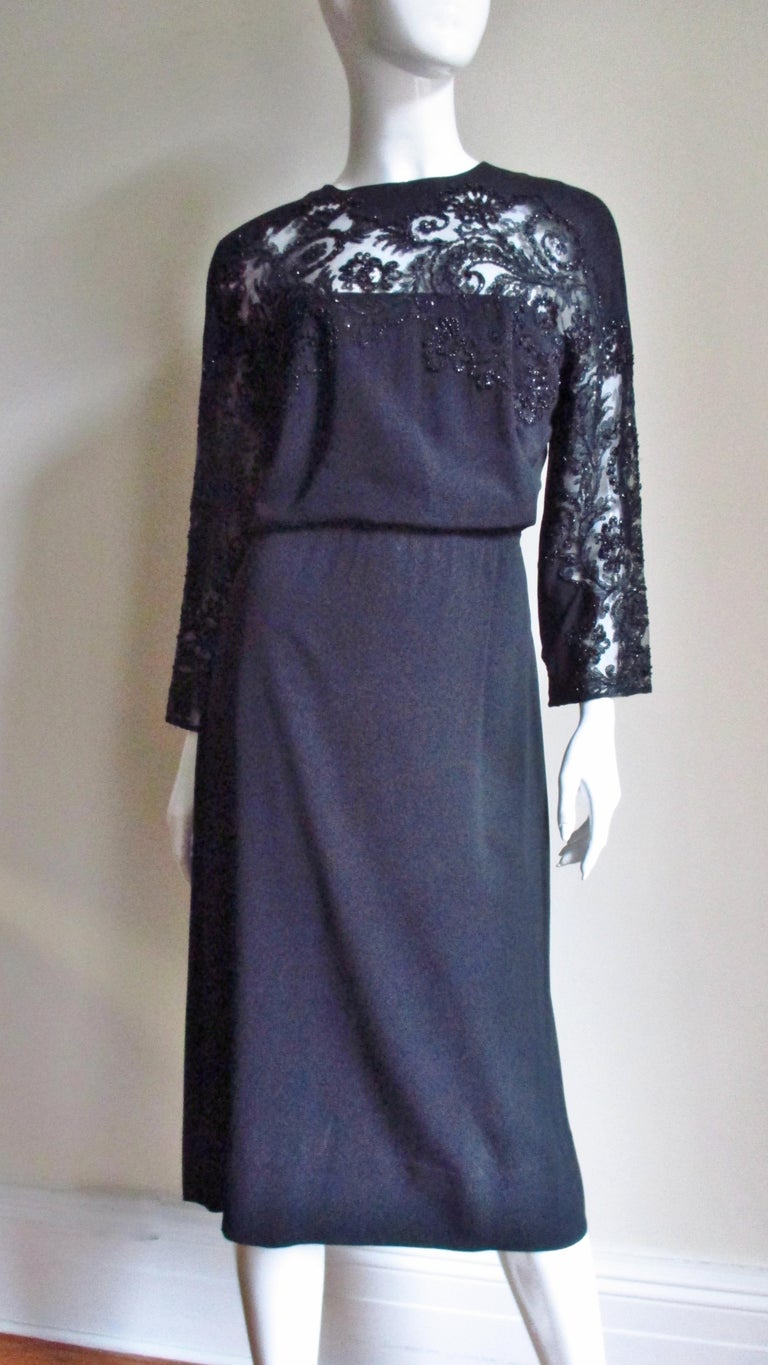 A beautiful black silk 1940s dress by Eisenberg Originals. It has a crew neckline, long sleeves and a stunning richly detailed glass seed beads lace insert across the chest and along the front of the gusseted dolman sleeves.  The skirt is slightly A