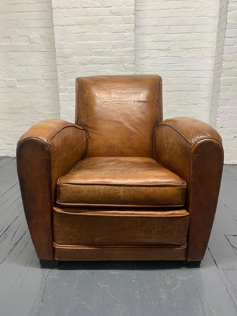 1940s French Art Deco leather lounge chair. The leather of the chair is in vintage condition with original patina. Chair has curved arms and wood legs.
