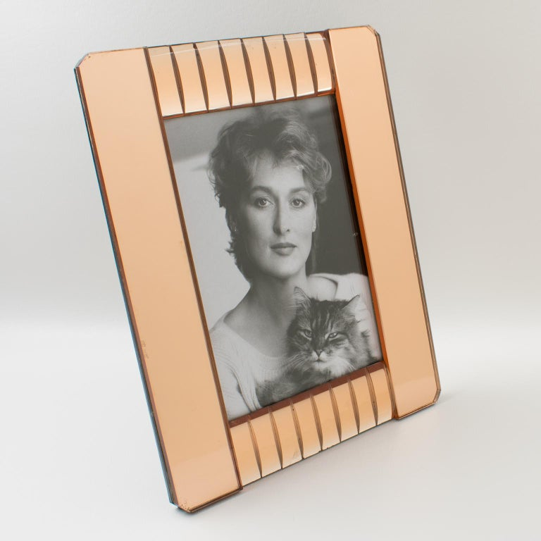 Elegant 1940s French mirrored picture photo frame. Deep geometric beveling and domed sides in lovely copper or pink peach color. Frame can only be placed in portrait position. Back and easel in decorative glossy black paper with crocodile skin