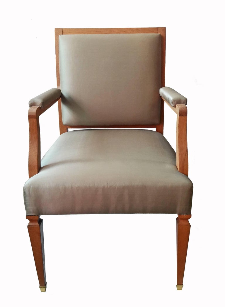 Two French armchairs, circa 1940, Empire style. Made of solid oak and upholstered in  iridescent taffeta. Original upholstery. Straight front legs with carved tops and bottom brass tips. Curved back legs. The elegant, straight lines of these chairs