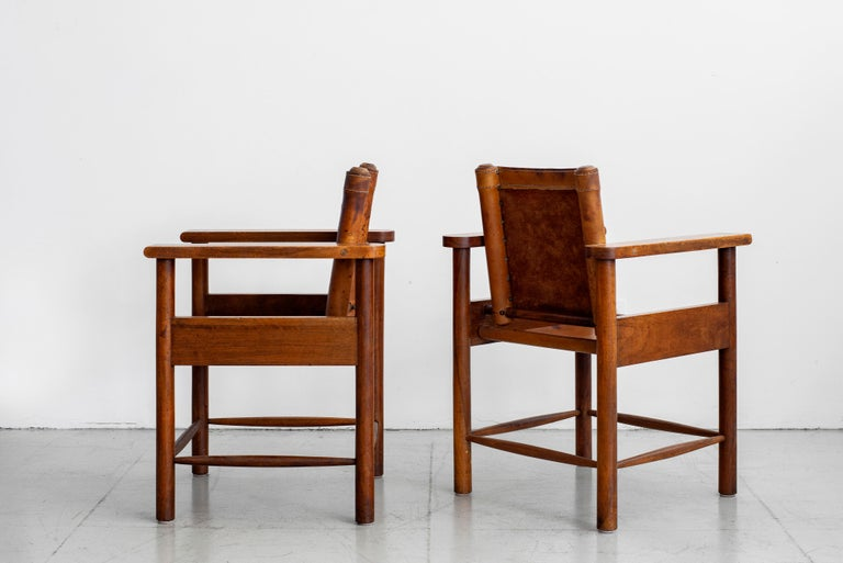 Fantastic pair of 1940s French leather chairs with plank oak armrests. Ornate detailing / construction with wonderful patina to leather and oak.