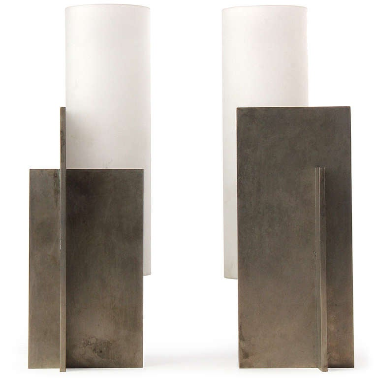 A striking and geometrically pure pair of Minimalist sconces formed from the intersection of two planes of patinated steel and the addition of a frosted glass column.