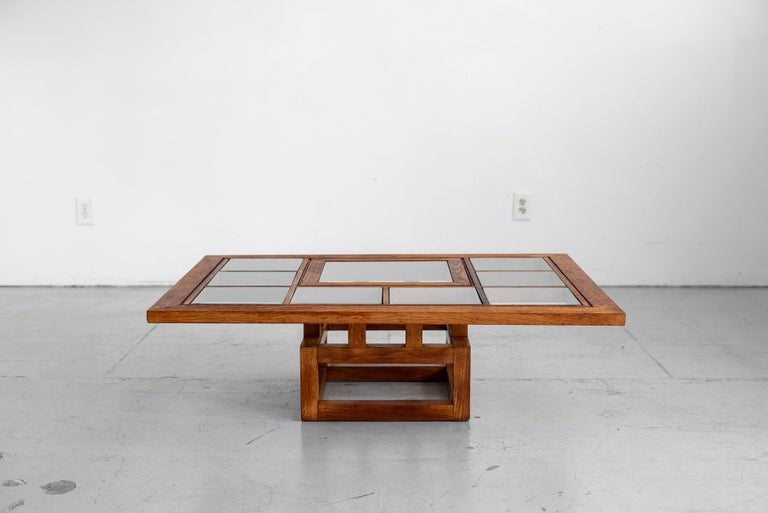 Beautiful French oak coffee table with clear square glass design on top. Cubist wood floating base and frame create a sculptural and airy piece.