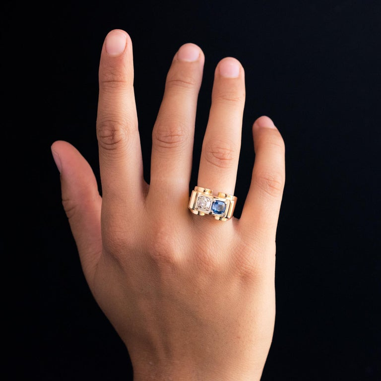 Ring in 18 karat yellow gold, eagle's head hallmark and platinum, dog's head hallmark. Called the tank bridge ring, this superb antique ring features an antique cushion- cut diamond on top and a natural blue cushion- cut sapphire. It has a spring