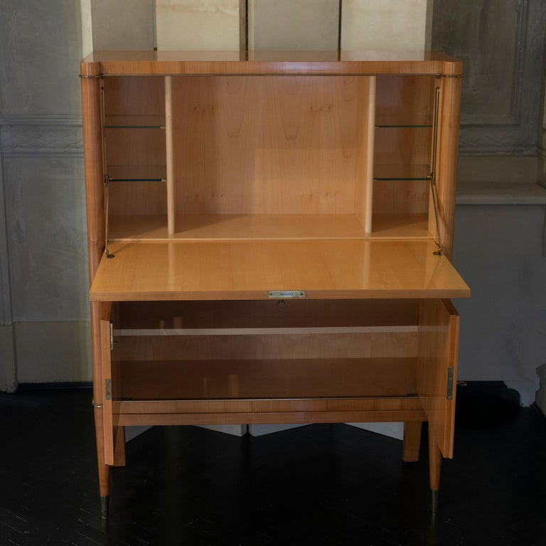 Lacquered birch wood secretaire, four glass shelves on the upper section and one adjustable shelve on the bottom section, brass details, perfect condition and vintage patina, France, circa 1940s.