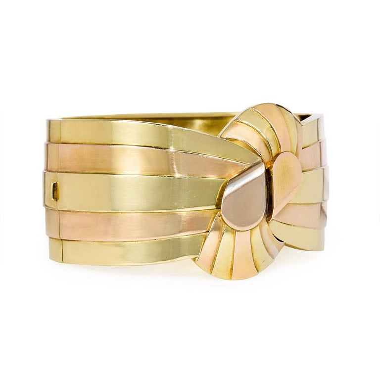 A Retro rose and yellow gold cuff bracelet of striped design, centering on a stylized bowknot, in 18k. France  Inner circumference approximately 7 3/4