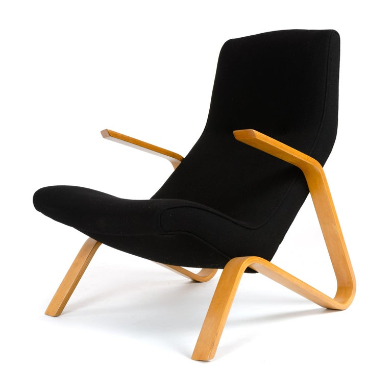An early lounge chair with original tufted upholstery on a laminated birch bentwood frame.