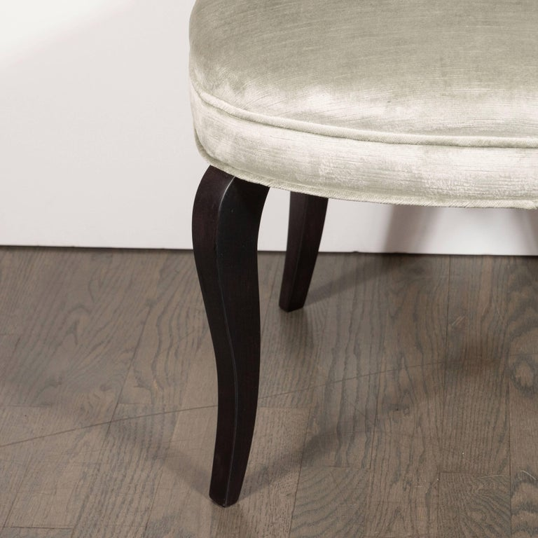 This glamorous and elegant vanity stool was realized in the United States, circa 1940. It features a scroll form channel back and cabriolet style legs in ebonized walnut. With its clean lines and dramatic silhouette, it would be a winning addition