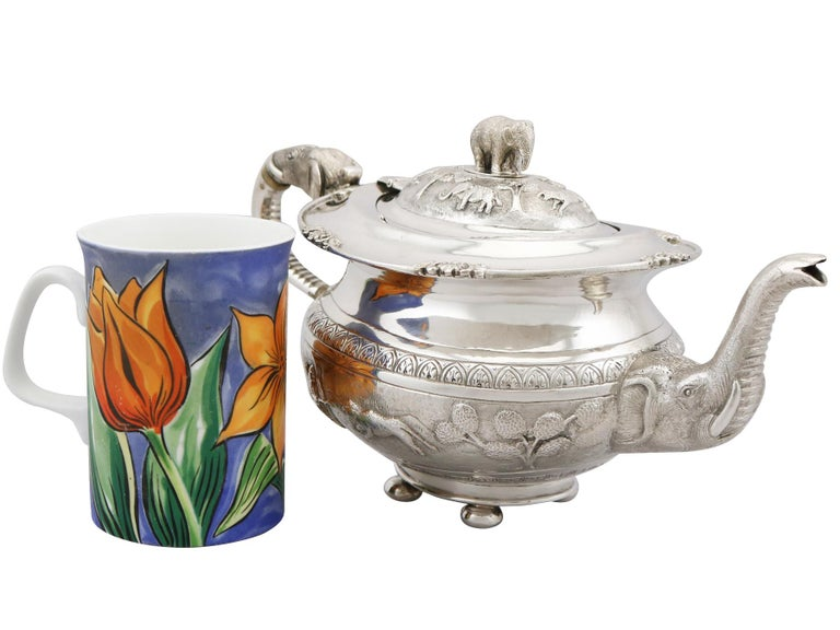 An exceptional, fine and impressive antique Indian silver teapot; an addition to our silver teaware collection.  This exceptional antique Indian silver teapot has a circular rounded, compressed form.  The body of the teapot is embellished with a