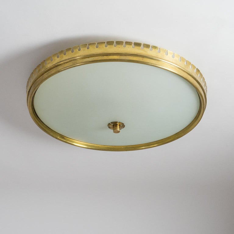 Beautiful Italian brass and satin glass flush mount from the 1940s attributed to Paolo Buffa. The main structure is constructed entirely of brass (lacquered an off-white on the inside) with a lovely sculpted and very uniquely scalloped rim. The back