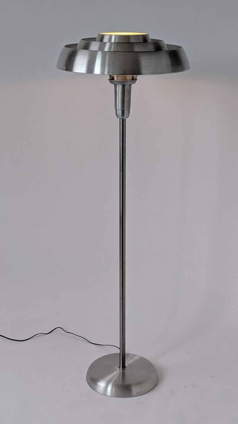 Bold futuristic Art Deco, machine age, streamline floor lamp.   The stacked ring does provide an efficient indirect lighting.   Well designed solid construction made of brushed spun aluminium.  Contain one E26 size socket rated at 300 watt.