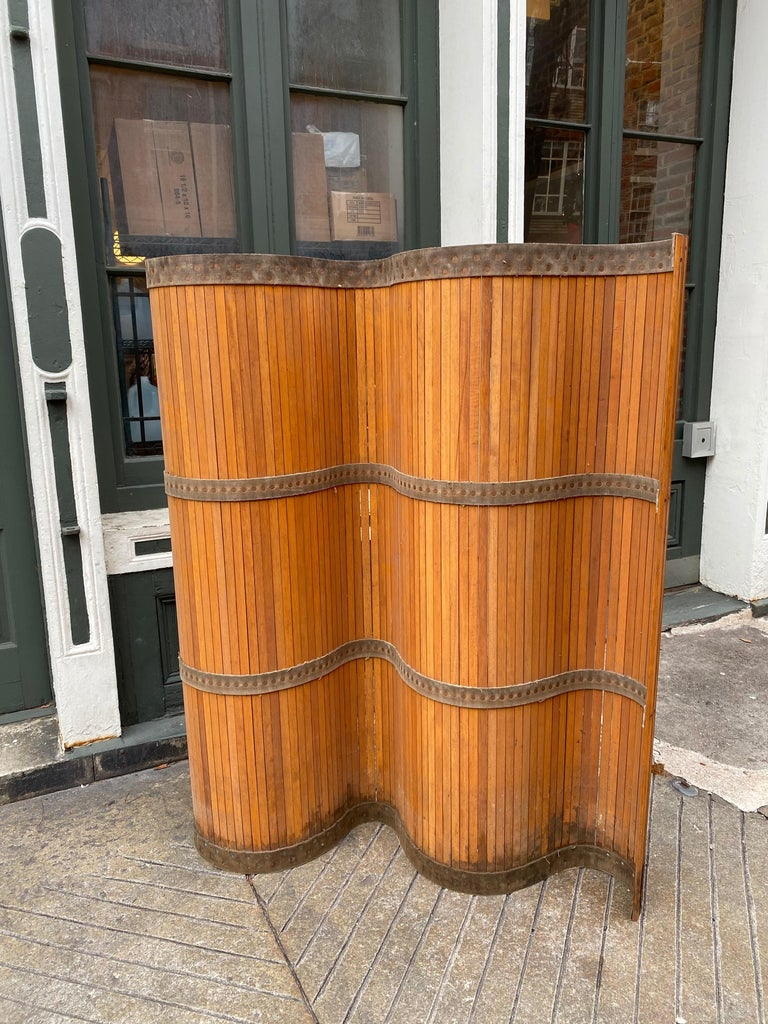 Industrial 1940s conveyor belt room screen made up of wood slats with rounded ends. Entire screen connected with canvas and rivets. Stands up very easily. Has a look somewhat like the Aaalto Screens. Bottom shows darker finish from getting wet at