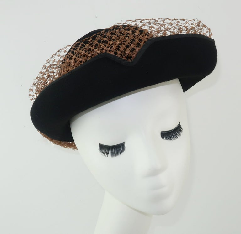 A stylish 1940's Miriam Lewis black wool felt hat with a vented crown, grosgrain trimmed brim and contrasting camel color netting with bow.  The unique rolled brim is nicely detailed with v-shaped cuts that add visual interest and serve as a channel