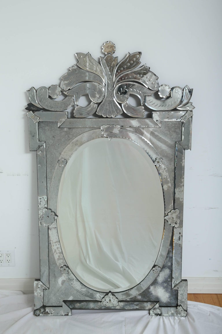 Exquisite large-scale Venetian mirror with beautiful hand etched designs throughout. The mirror features a stunning oval centre within a shield shaped frame. Pediment top features ornate scrolled designs. Has antique glass borders in hues of smoked