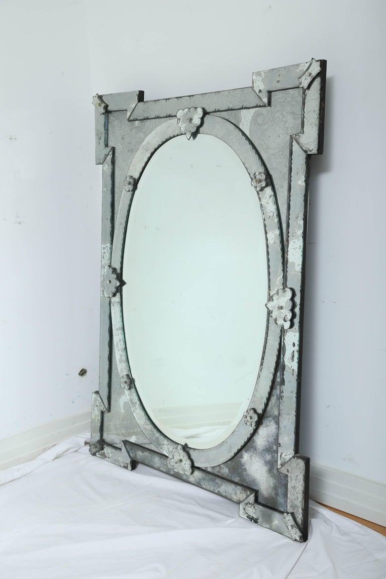 Exquisite large scale Venetian mirror with beveled edges and beautiful hand etched designs throughout. The mirror features a stunning oval center within a shield shaped frame.  Stunning Hollywood Regency, Baroque Revival  design, mixing well with