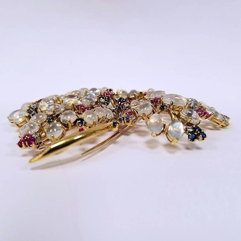 A Mid-20th Century French 18 karat gold brooch with moonstones, sapphires, rubies and diamonds attributed to John Rubel Paris. The brooch has 60 oval cabochon moonstones with an approximate total weight of 45.00 carats, 40 round-cut sapphires with