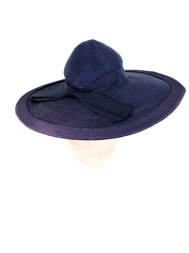 1940s Navy wide brimmed-hat made of a woven and coated straw. The wide brim is trimed with a secondary ring of straw, the high crown is adorned with a grosgrain ribbon, woven patterned button, and an enlarged bow. The crown is small as this hat is