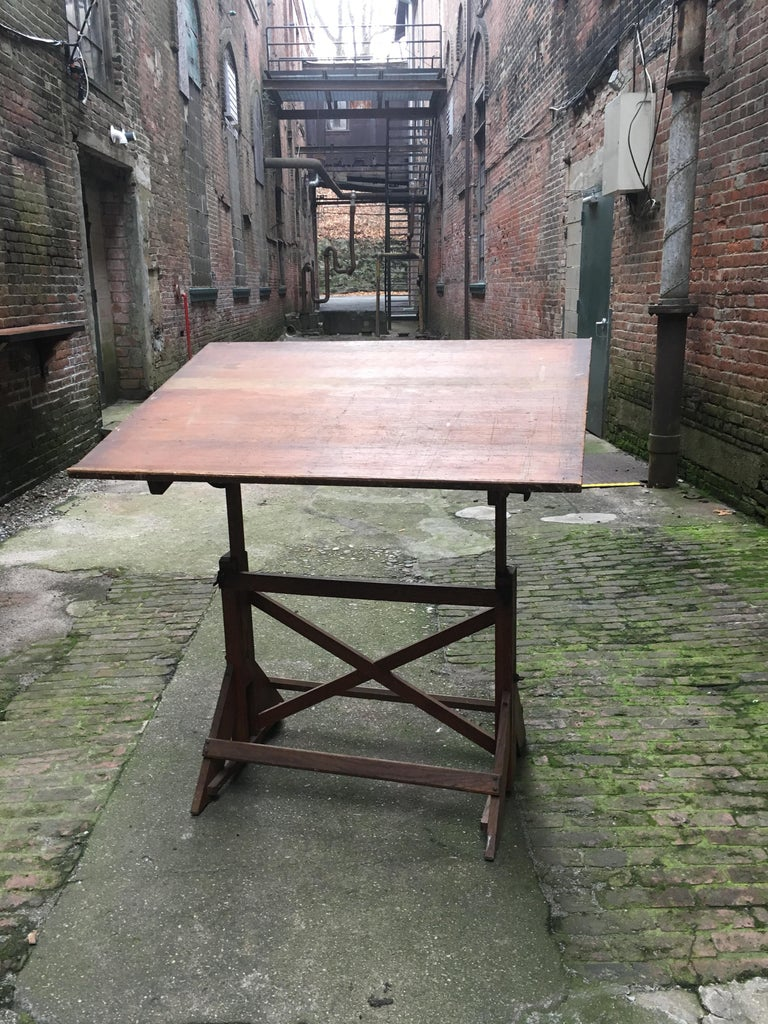 Fully adjustable height and angle. Featuring a solid oak base with pine work surface and iron hardware. The drafting table comes from the estate of marine, landscape and illustrator, Anton Otto Fischer, Woodstock, NY. Wonderful patina and overall