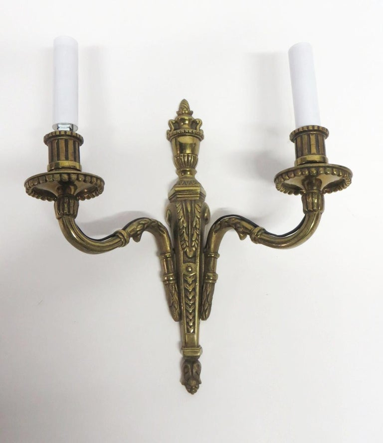 Bronze two arm candlestick sconces with an antique bronze patina from the 1940s. Priced as a pair. This can be seen at our 400 Gilligan St location in Scranton, PA.