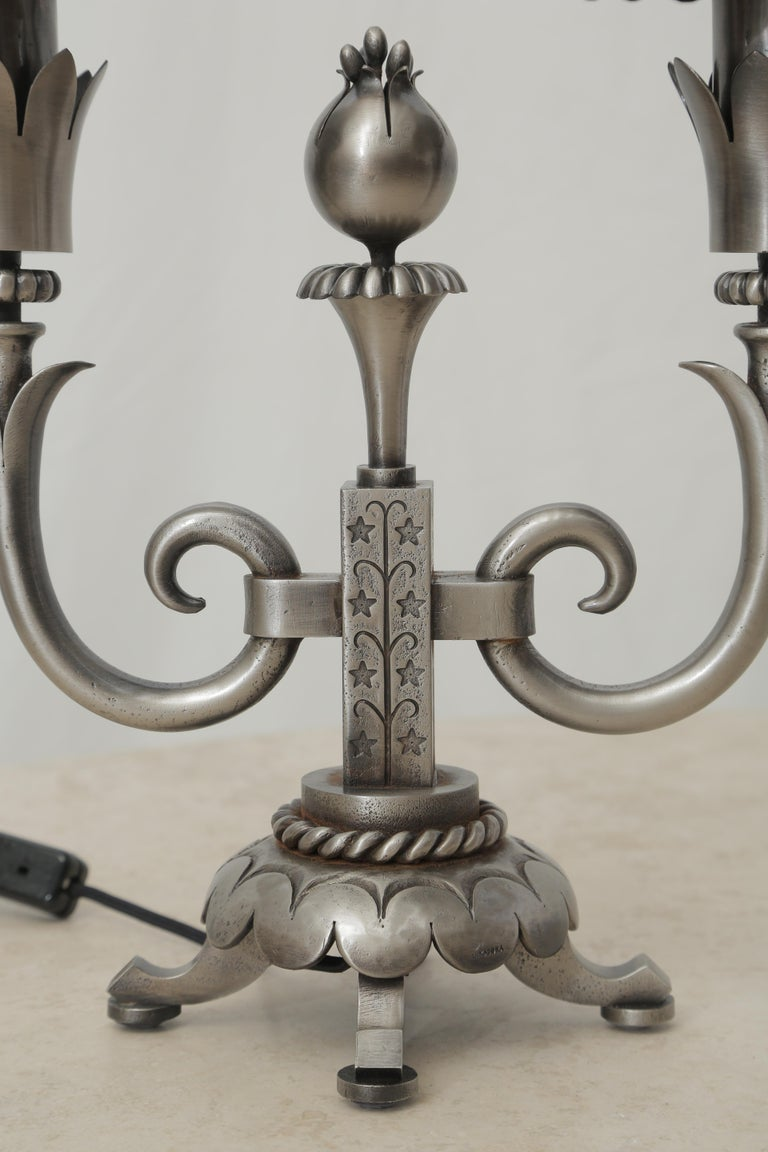 Wrought iron pair of table lamps attributed to Gilbert Poillerat, circa 1940, recently cleaned and polished. Very harmonious sculpture details with the rope around the base of each piece and the pomegranate fruit in the central part of each lamp,