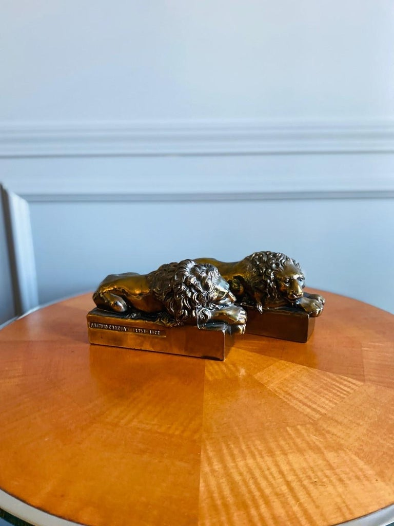 """Pair of 1940s polished bronze plated metal lion bookends. Signed: """"Antonio Canova. 1757-1822."""" These lions were originally sculpted by Antonio Canova (Italian, 1757-1822) in larger scale for the tomb of Pope Clement XIII in St. Peter's Basilica. The"""