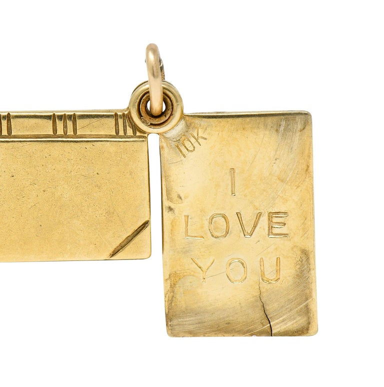 Charm is designed as a book with deeply engraved cover details  It swivels open to reveal the engraved words 'I Love You'  Completed by jump ring bale  Stamped 10K for 10 karat gold  Circa: 1940s  Measures: 3/8 x 5/8 inch  Total weight: 1.6