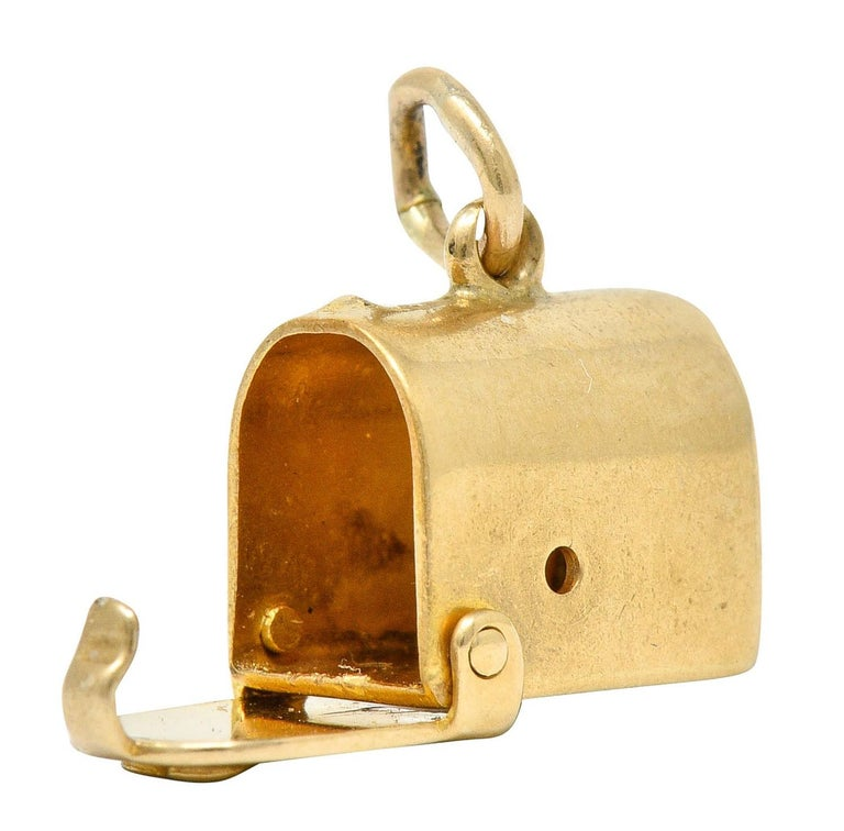 Designed as a planished mailbox form  With a front facing heart on its door  Which opens on a hinge  Completed by a jump ring bale  Stamped 14K for 14 karat gold  Circa: 1940s  Measures: 1/4 x 3/8 inch  Total weight: 1.4 grams  Deliverable.