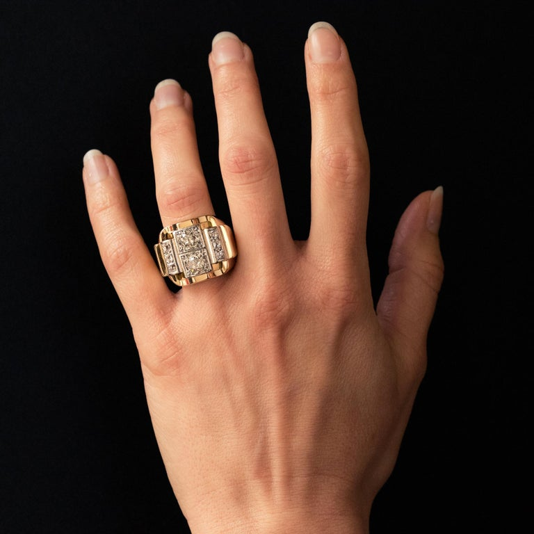 Tank ring in 18 karat yellow gold, and platinum, owl and mascaron hallmarks. Voluminous and geometric, this tank ring is decorated with 2 antique- cut diamonds supported by two lines of 2x3 antique brilliant- cut diamonds, all in platinum set. Total