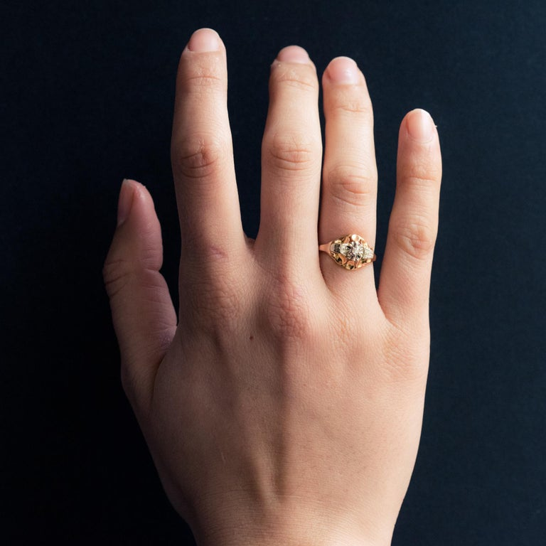 Ring in 18 karat yellow gold, eagle's head hallmark. Lovely antique ring, it is set with a diamond, bordered on both sides with petals and supported by 2 chiseled white gold bridges. Diamond weight: about 0.02 carat. Height: 10.4 mm, width: 13.2 mm,