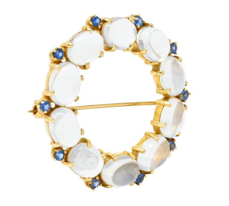 Wreath style brooch comprised of ten oval cabochon moonstones measuring approximately 9.0 x 6.5 mm, transparent with strong billowing blue adularescence   Accented by round cut sapphire weighing approximately 1.00 carat total, transparent and
