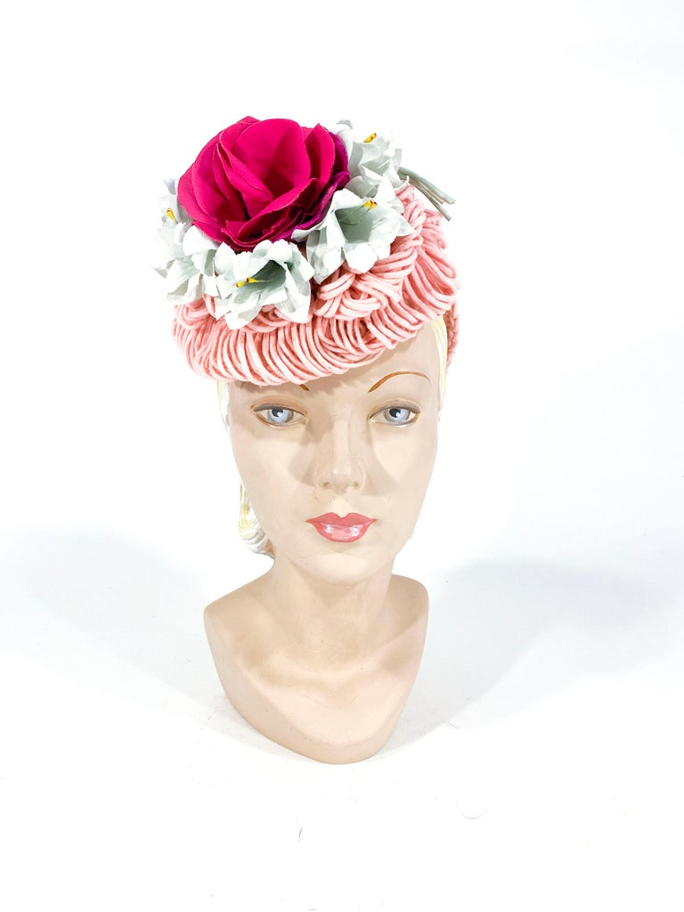 1940's handmade rose pink crochet wool cocktail hat with layers of wool loops, pale blue flowers, and centered with a large dark silk rose with velvet petals. The security ring fixes the hat on to the head and is covered with decorative crochet.
