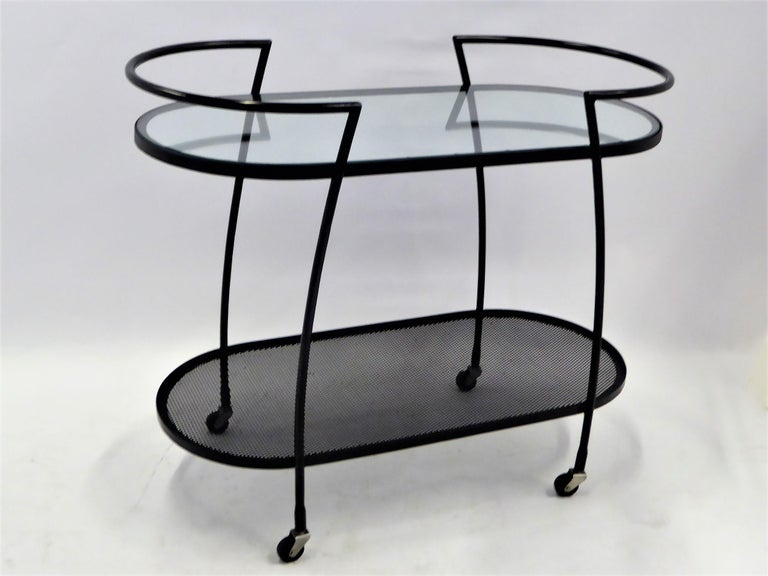 1940s streamline moderne wrought iron rolling cart with an inset glass shelf above and metal screen shelf below. The racetrack oval shape has shaped arms that continue down the sides as legs. New glass and wrought iron re-patinated. After the styles