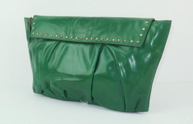 This 1940's emerald green leather handbag has a fashion forward look with brass faceted stud accents that are as stylish today as in the past.  The trapezoidal silhouette and ruched leather body are eye catching details and the manageable size is