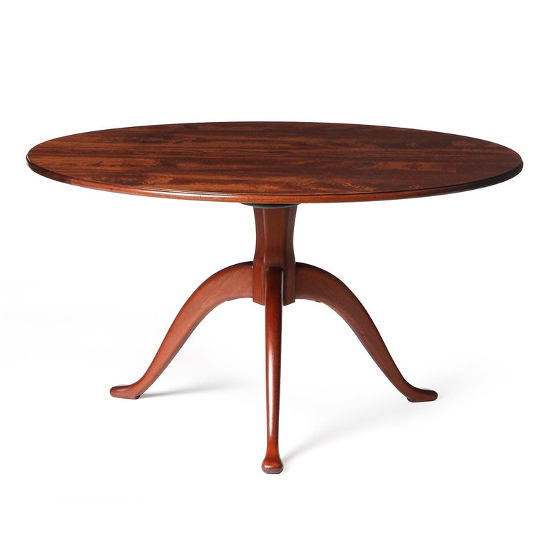 A remarkable and elegant Cuban mahogany round center table with a sculpted tripod base.