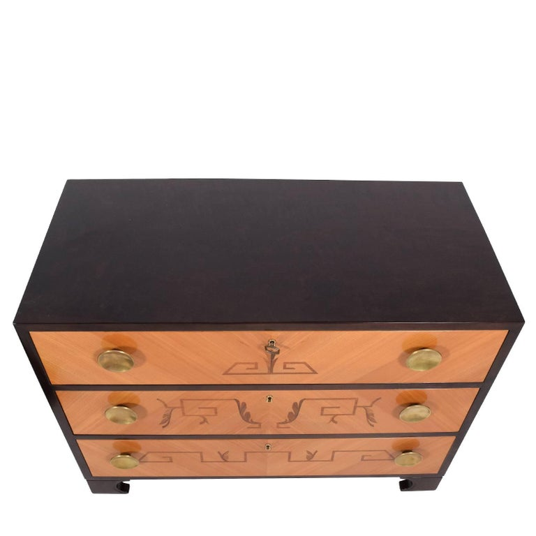 Features three drawers with Art Deco inlay designs and solid brass pulls.