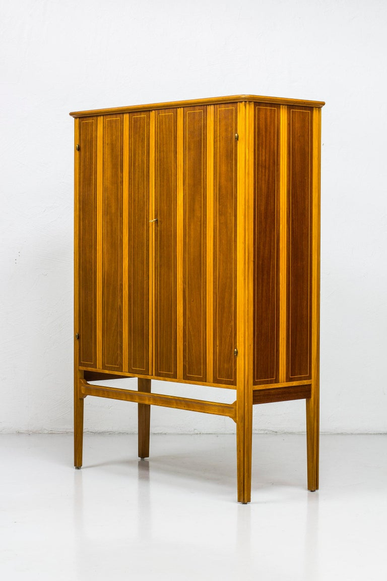 Exceptional Swedish modern cabinet. Made in Sweden during the 1940s. Made from solid beech and teak wood. Embossed pattern on the doors as well as a Fine marquetry line of lighter wood on the teak parts. Brass details and original key. Possibility
