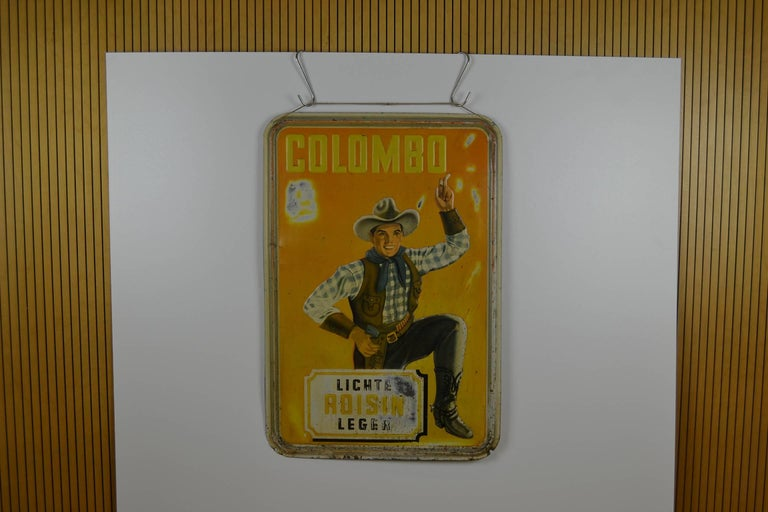 Very rare Large original Tin Advertising Sign   for Colombo Cigarettes - Colombo Smokes - Colombo Tobacco .  This Publicity Sign has an awesome design: a smoking Cowboy dressed in Cowboy clothes , Cowboy hat, belt with gun and cowboy boots.  This