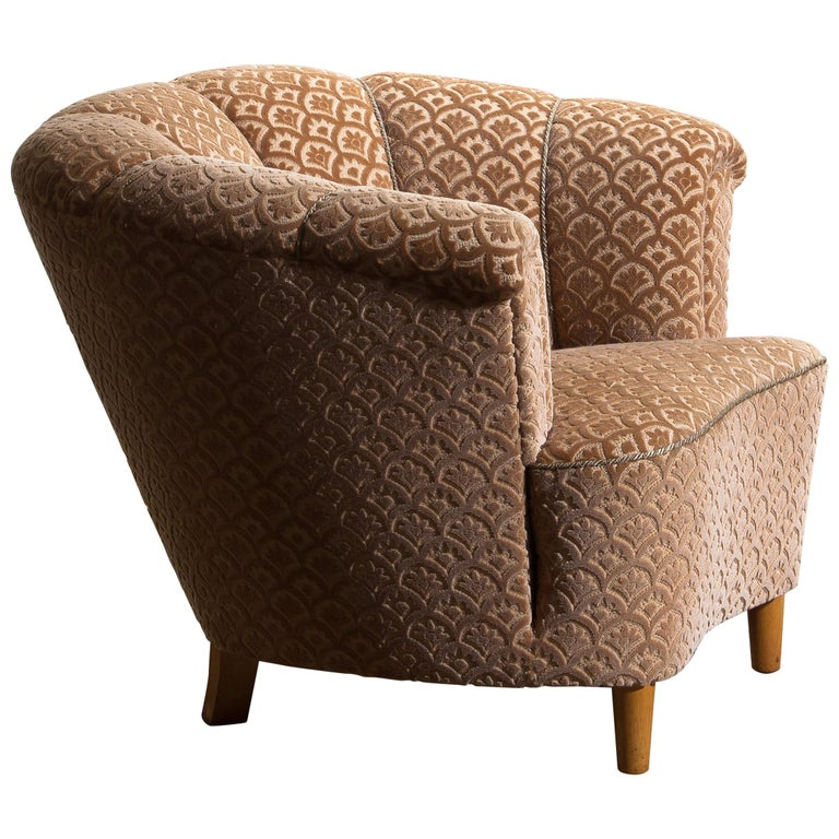 Beautiful and comfortable club or lounge or cocktail chair from the 1940s. In original and excellent condition. The chair is richly upholstered in flocked velvet and standing on beech legs. We have two chairs in stock. Both are in excellent