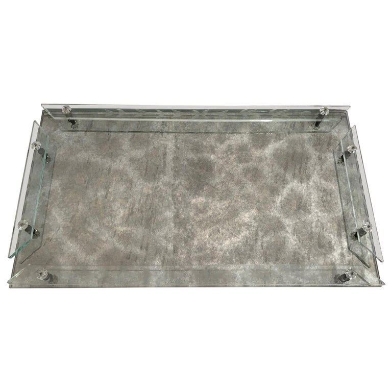 Hollywood Regency and Art Deco era Venetian mirrored tray with smokey grey antique cast and veining. The vanity tray is fitted with art glass gallery rails featuring elegant hand etched floral designs, and features glass rosette accents. Perfect for