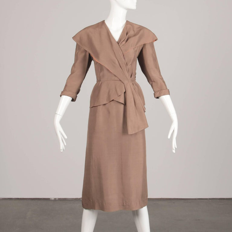 Asymmetric beige silk women's suit from the 1940s. The skirt is unlined with side metal zip and hook closure. 100% silk. Fits like a size small. The waist measures 25.75