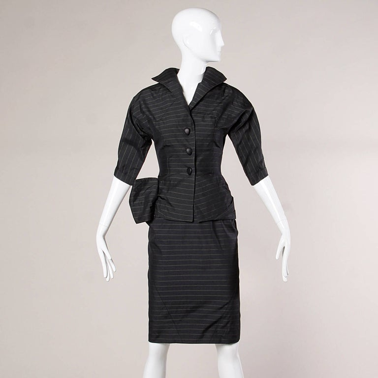 Absolutely stunning vintage 1940's couture suit featuring hand stitched silk lining, highest quality silk and wool blend fabric and an incredibly sleek 1940s silhouette with an asymmetric bow detail on the jacket. Both pieces can be worn separately