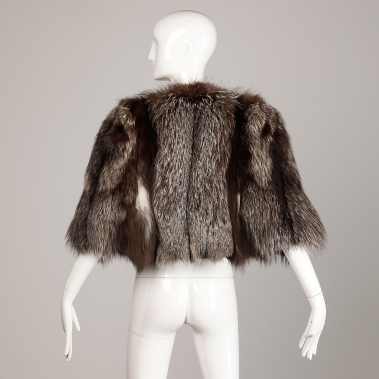 Beautiful vintage 1940s crystal fox fur cape with arm slits and black satin lining. Gorgeous coloring with a flattering design. Excellent vintage condition with normal signs of wear for a fur of this age. One of the arm straps is missing from the