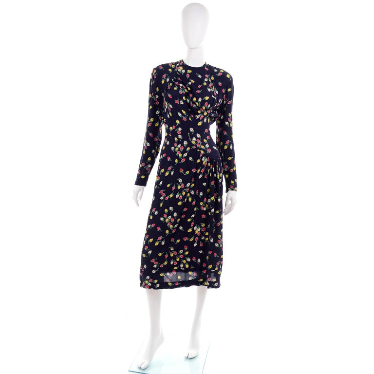 This is a great 1940;s  vintage navy midi dress with a colorful rosebud print. The pretty roses are in shades of pink, yellow and white with green stems. This dress is easy to assimilate into a modern wardrobe and has long sleeves, a gathered