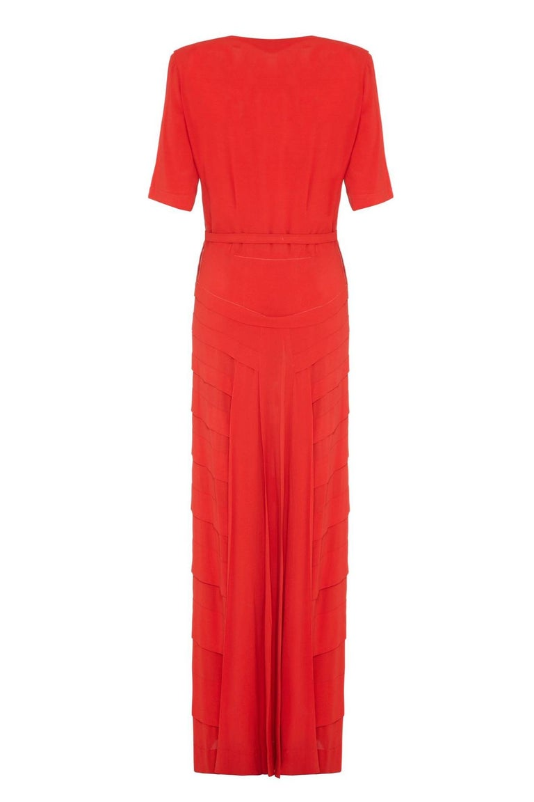 This sensational 1940s deep coral colour lightweight wool/rayon crepe gown with original matching belt is in absolutely excellent vintage condition for a piece of this era. The dress features an attractive square neckline embellished with a single