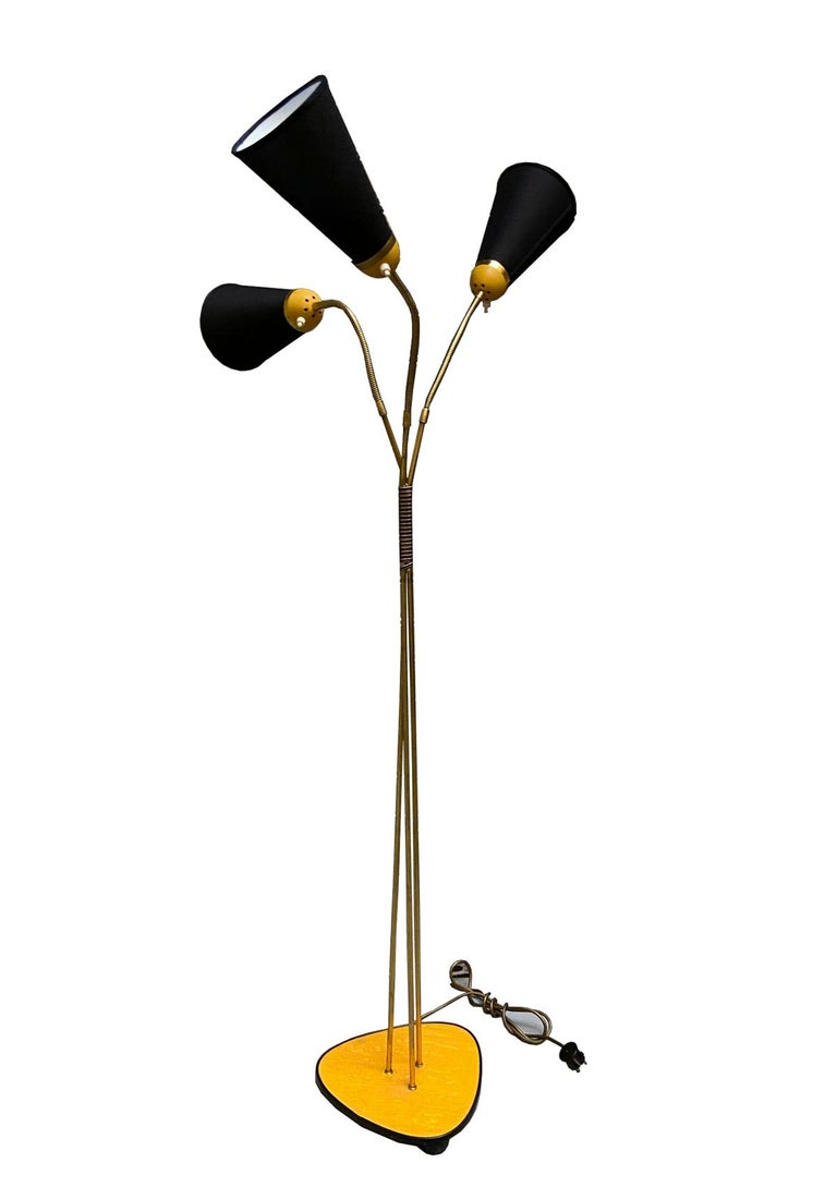 Beautiful midcentury brass floor lamp with wooden base and three black shades. Curved arms with embossed stripes. The height and the angle of the shades can be adjusted.
