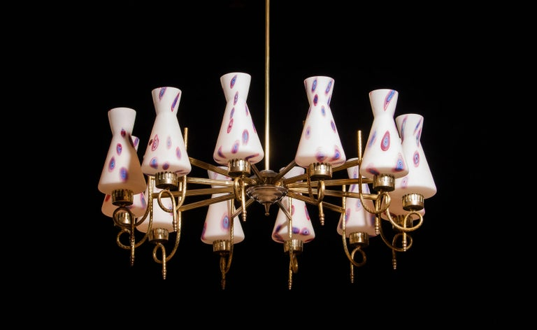 Magnificent large chandelier. This lamp is made of a beautiful brass with polished aluminium shape with twelve white designed Murano glass shades. The shades are labelled. It is in an excellent working condition. Period 1940s Dimensions: H.90