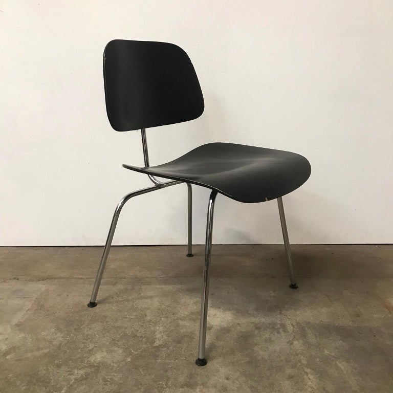 DCM in black by Herman Miller. The chair shows traces of wear like some loss of paint/lacquer and has some tiny stains of paint (light yellow) on the sea and backrest. Also two chips of wood are missing on the backrest and one on the seat. Black